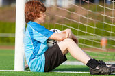 Sad looking boy leaning at goal — Stock Photo