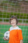 Smiling young soccer player standing against goal — Stock Photo