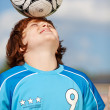 Boy balancing soccer ball on his head — Stock Photo