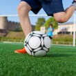 Stock Photo: Boy kicking soccer ball on field