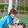 Stock Photo: Boy Giving Piggyback Ride To Friend In Soccer Field