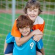 Boy Giving Piggyback Ride To Friend On Soccer Field — Stock Photo
