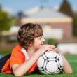 Boy With Soccer Lying On Field While Looking Away — Stock Photo