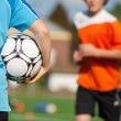 Boy Holding Soccer Ball With Friend Running In Background — Stock Photo