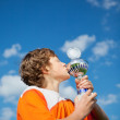 Little Boy Kissing Trophy Against Sky — Stock Photo #27100803