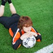 Stock Photo: Little Boy With Soccer Lying On Field