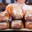 Worker stacking bread in a bakery — Stock Photo