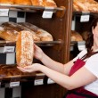 Smiling bakery assistant showing a loaf of bread — Stock Photo #27103417
