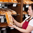 Bakery worker with fresh crusty bread — Stock Photo #27103421