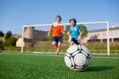 Two young soccer players running to soccer ball — Stock Photo