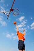 Jongen spelen basketbal tegen blauwe hemel — Stok fotoğraf