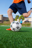 Boy kicking soccer ball on field — Stock Photo