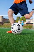 Chłopiec kopanie piłki na pole — Zdjęcie stockowe