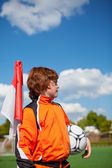 Niño con balón de fútbol mientras miras lejos bandera esquina — Foto de Stock
