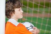 Niño con balón de fútbol mientras apoyado en poste neto — Foto de Stock