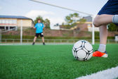 Boy Kicking Soccer Ball With Goalkeeper In Background — Stock Photo
