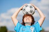 çocuğun futbol topu kafasına gökyüzü karşı elinde — Stok fotoğraf
