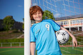 Boy Holding Soccer Ball While Leaning On Net Pole — Stock Photo