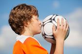 Boy Kissing Soccer Ball Against Sky — Stock Photo