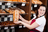 Smiling bakery assistant showing a loaf of bread — Stock Photo