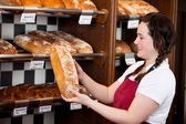 Bakery worker with fresh crusty bread — Stock Photo