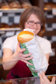 Smiling saleswoman with bread rolls — Stock Photo