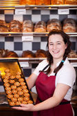 Smiling bakery assistant with biscuits — Stock Photo
