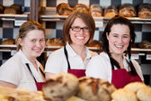 Three happy bakery workers — Stock Photo