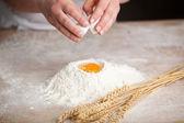 Breaking an egg into flour — Stock Photo