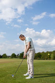 Mature man teeing off — Stock Photo