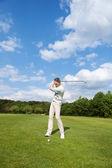 Hombre maduro jugando al golf en curso — Foto de Stock