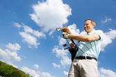 Man Removing Golf Club Against Sky — Stock Photo