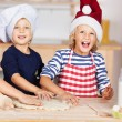 Stock Photo: Girl Using Cookie Cutters On Dough With Sisters At Kitchen Count