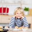Girl leaning at the kitchen table with muffins — Stock fotografie