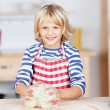 Happy little blond girl kneading dough — Stock Photo
