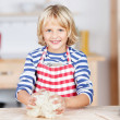 Happy little blond girl kneading dough — Stock Photo #27170295
