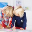 Stock Photo: Two sisters learning to write