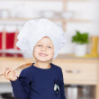 Girl Holding Wooden Spoon While Baking Cupcakes At Kitchen Count — Stock Photo #27170809