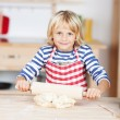 Stock Photo: Girl Rolling Dough On Kitchen Counter