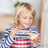 Little girl glazing a cupcake — Stock Photo