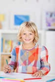 Small young girl smiling and drawing a picture — Stock Photo