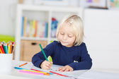 Small young girl drawing a picture in kindergarten — Stock Photo