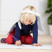 Young girl in angel wings drawing on the floor — Stock Photo