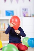 Playful girl hiding behind a red balloon — Stock Photo