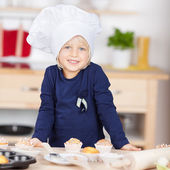 Cute little blond girl in a chefs toque — Stock Photo