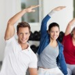 Group Doing Stretching Exercise In Gym — Stock Photo #27195117