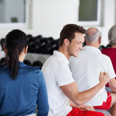 Homme, muscles de la flexion assis avec la famille dans la salle de gym — Photo