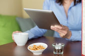 Woman reading from a tablet in the coffee shop — Stock Photo