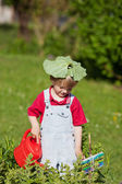 Boy Watering Plants With Leaf On Head In Yard — Stock Photo