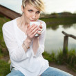 Woman Holding Warm Coffee Cup By The Lake — Stock Photo